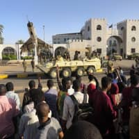 Sudanese protesters flash the victory sign at a passing military vehicle as they gather for a second day outside the military headquarters in Khartoum on Sunday. | AFP-JIJI