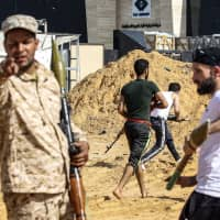 Libyan fighters loyal to the Government of National Accord (GNA) run during clashes with forces loyal to strongman Khalifa Hifter south of the capital Tripoli's suburb of Ain Zara, on Wednesday. | AFP-JIJI