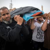 Libyans carry the body of a fighter loyal to the Government of National Accord (GNA) during his funeral in Tripoli on Wednesday after he was reportedly killed during clashes with forces loyal to strongman Khalifa Haftar in al-Hira region, about 70 km south of Tripoli. | AFP-JIJI
