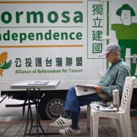 A pro-Taiwan independent activist reads a newspaper in front of a truck outside parliament in Taipei on March 19. | AFP-JIJI