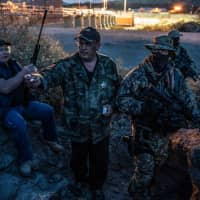 UCP members (from left) Jeff Allen, Jim Benvie, Viper and Stinger share cigarettes while patroling the U.S.-Mexico border in Sunland Park, New Mexico, on March 20. The American Civil Liberties Union denounced the militia's actions in a letter on April 18 that asked New Mexico's governor and attorney general to investigate the group. | AFP-JIJI