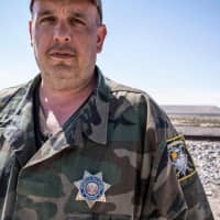 United Constitutional Patriots New Mexico Border Ops militia team member Jim Benvie, 43, from Minnesota, looks on near the U.S.-Mexico border wall in Anapra, New Mexico, on March 20. | AFP-JIJI