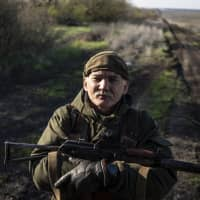 A Ukrainian serviceman guards a position near the front line in the Donetsk region on Sunday as Ukrainians voted amid continuing conflict. | AP