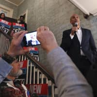 Democratic presidential candidate Sen. Cory Booker addresses a gathering as guests take photographs with their phones at a house party during a campaign stop in Claremont, New Hampshire, on March 15.   AP