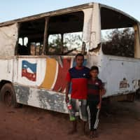 Venezuelans Angel Valderrama, 41, who was a construction worker, poses with his son, Erasmo, outside of an abandoned bus in the border city of Pacaraima, Brazil, Sunday. | REUTERS