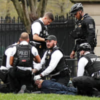 Police and rescue personnel tend to a man in Lafayette Park in Washington after the man lit his jacket on fire in front of the White House on Friday.   REUTERS