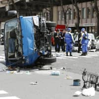 Police investigate an accident Friday in which a car struck pedestrians and a garbage truck in the Ikebukuro district of Tokyo, leaving 10 people injured, two of them in critical condition. | KYODO