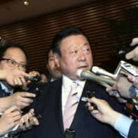 Yoshitaka Sakurada, former Olympic minister, is surrounded by reporters after submitting a letter of resignation to Prime Minister Shinzo Abe on Wednesday at the Prime Minister's Office. | KYODO