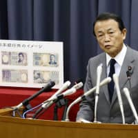 Finance Minister Taro Aso announces new designs for ¥10,000, ¥5,000 and ¥1,000 bills during a news conference at the Finance Ministry in Tokyo on Tuesday. | KYODO