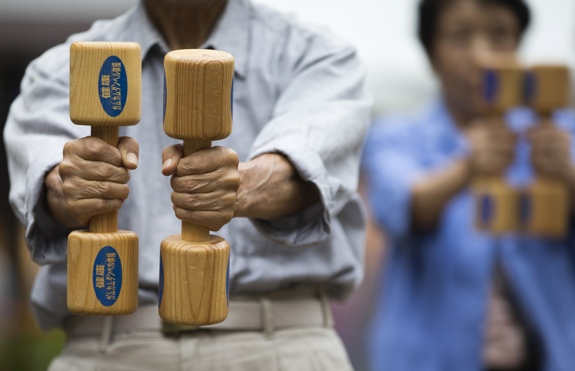 People exercise with wooden dumbbells during an event marking Respect for the Aged Day at a temple in the Sugamo district of Tokyo in September 2016. A new report has said that a quarter of Japan's breadwinners will turn 75 or older by 2040. | BLOOMBERG