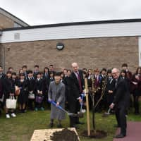 Miho Obi (left), a teacher from Hikawa High School in Yamanashi Prefecture, and Andrew Harris (center), head teacher at Katharine Lady Berkeley's School near Bristol, England, take part in a cherry tree planting ceremony at the school last month. | KYODO