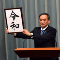 Chief Cabinet Secretary Yoshihide Suga holds up a placard showing Reiwa, the name of the next Imperial era, at the Prime Minister's Office on Monday. | SATOKO KAWASAKI