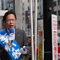 Writer Lee Komaki, originally from China, makes a speech on a street in Kabukicho, a red-light district in Shinjuku Ward, Tokyo, on April 19. | CHISATO TANAKA