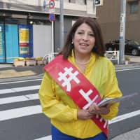 Bolivia-born Noemi Inoue hands out flyers to prospective voters in Sumida Ward, Tokyo, on April 19. | CHISATO TANAKA