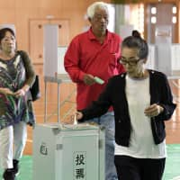 Voters cast their ballots for candidates in a Lower House by-election in the city of Okinawa on Sunday. | KYODO