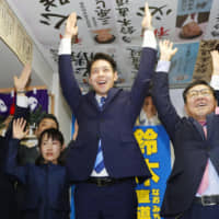 Naomichi Suzuki celebrates with supporters on Sunday in Sapporo after winning the Hokkaido gubernatorial election. | KYODO