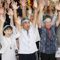 Tomohiro Yara (center), supported by the opposition camp, celebrates his victory in the Lower House by-election in Okinawa on Sunday with Okinawa Gov. Denny Tamaki (second from right) and other supporters. | KYODO