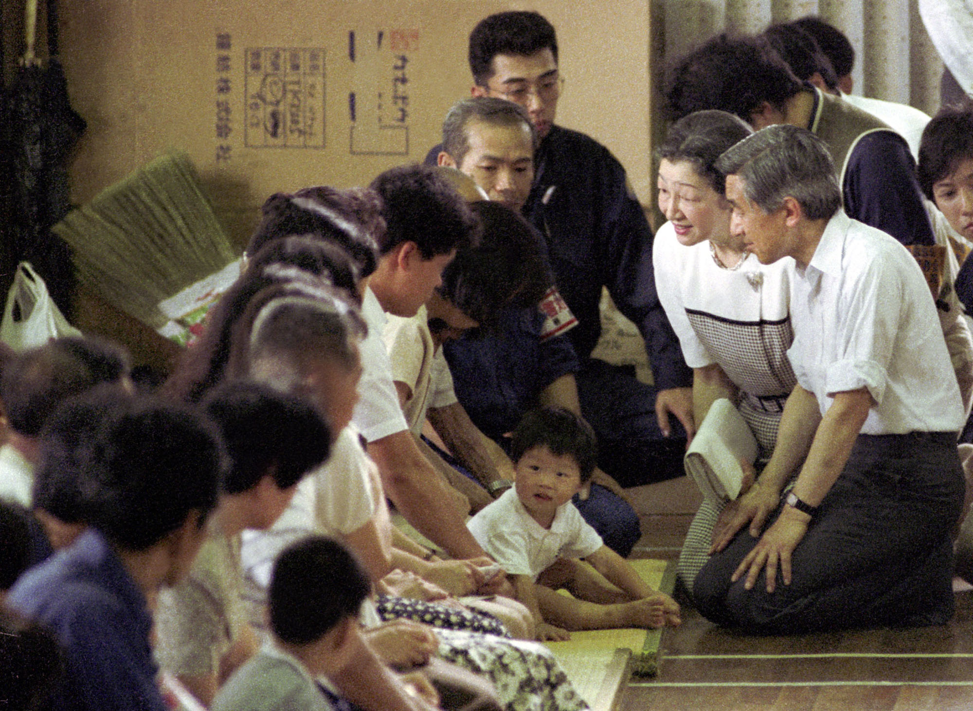 Emperor Akihito and Empress Michiko kneel on the floor to meet with evacuees at a shelter in Shimabara, Nagasaki Prefecture, in July 1991 after the eruption of Mount Unzen. | KYODO