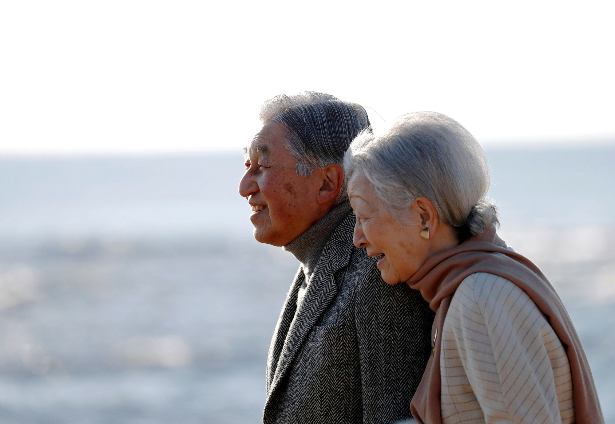 Emperor Akihito and Empress Michiko stroll on a beach near their Imperial villa, where they were staying for the Emperor's recuperation, in Hayama, Kanagawa Prefecture, on Jan. 21. | REUTERS