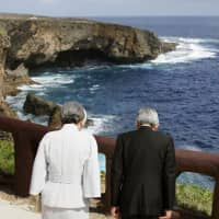 Emperor Akihito and Empress Michiko offer prayers to victims of the 1944 Battle of Saipan at 'Banzai Cliff' at the northern end of Saipan on June 28, 2005. The cliff was named after the cry 'Tenno Heika, banzai' ('Long live the Emperor') that the Japanese shouted before throwing themselves over the edge. | POOL / VIA KYODO