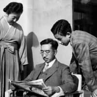 Emperor Hirohito, posthumously known as Emperor Showa, reads a newspaper next to Empress Kojun and Crown Prince Akihito at the Imperial Palace in Tokyo in this photo taken in the 1950s. | AFP-JIJI