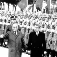 Chinese President Yang Shangkun leads Emperor Akihito as they review an honor guard during a welcome ceremony outside Beijing's Great Hall of the People on Oct. 23, 1992. The Japanese government saw the Emperor's visit to China as an opportunity to heal wounds left by Japan's wartime aggression. | AP