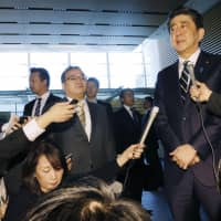 Prime Minister Shinzo Abe speaks to reporters Monday morning at his office ahead of the highly anticipated announcement of Japan's new era name. | KYODO