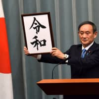 Chief Cabinet Secretary Yoshihide Suga holds up a placard showing the kanji for Reiwa, the name of the next Imperial era, during a news conference Monday at the Prime Minister's Office in Tokyo. | SATOKO KAWASAKI
