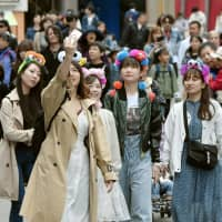 Women take a selfie on their way to Universal Studios Japan in Osaka on Saturday, the first day of the 10-day Golden Week holiday. | KYODO