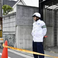 A police officer stands near a residential area in Yokohama where a man snatched a gun from another officer and fired it. No one was injured. | KYODO