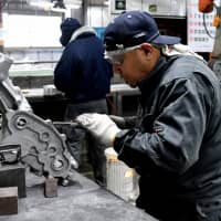 Dexter Tan Dimaapia, an employee from the Philippines at Sakae Casting Co., works at the firm's aluminum-casting plant in Hachioji, western Tokyo, on Jan. 29. | YOSHIAKI MIURA
