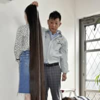 Keito Kawahara, 18, from Izumi, Kagoshima Prefecture, who used to hold the record as the teenager aged 13-17 with the longest hair in the world, has the length of her hair measured prior to her first-ever haircut on Tuesday.   KYODO