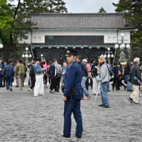 A policeman stands guard as people gather outside the Imperial Palace in Tokyo on Tuesday. | AFP-JIJI