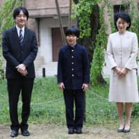Prince Hisahito and his parents, Prince Akishino and Princess Kiko, pose for photos at Ochanomizu University Junior High School before attending an entrance ceremony in Tokyo on April 8. | AFP-JIJI