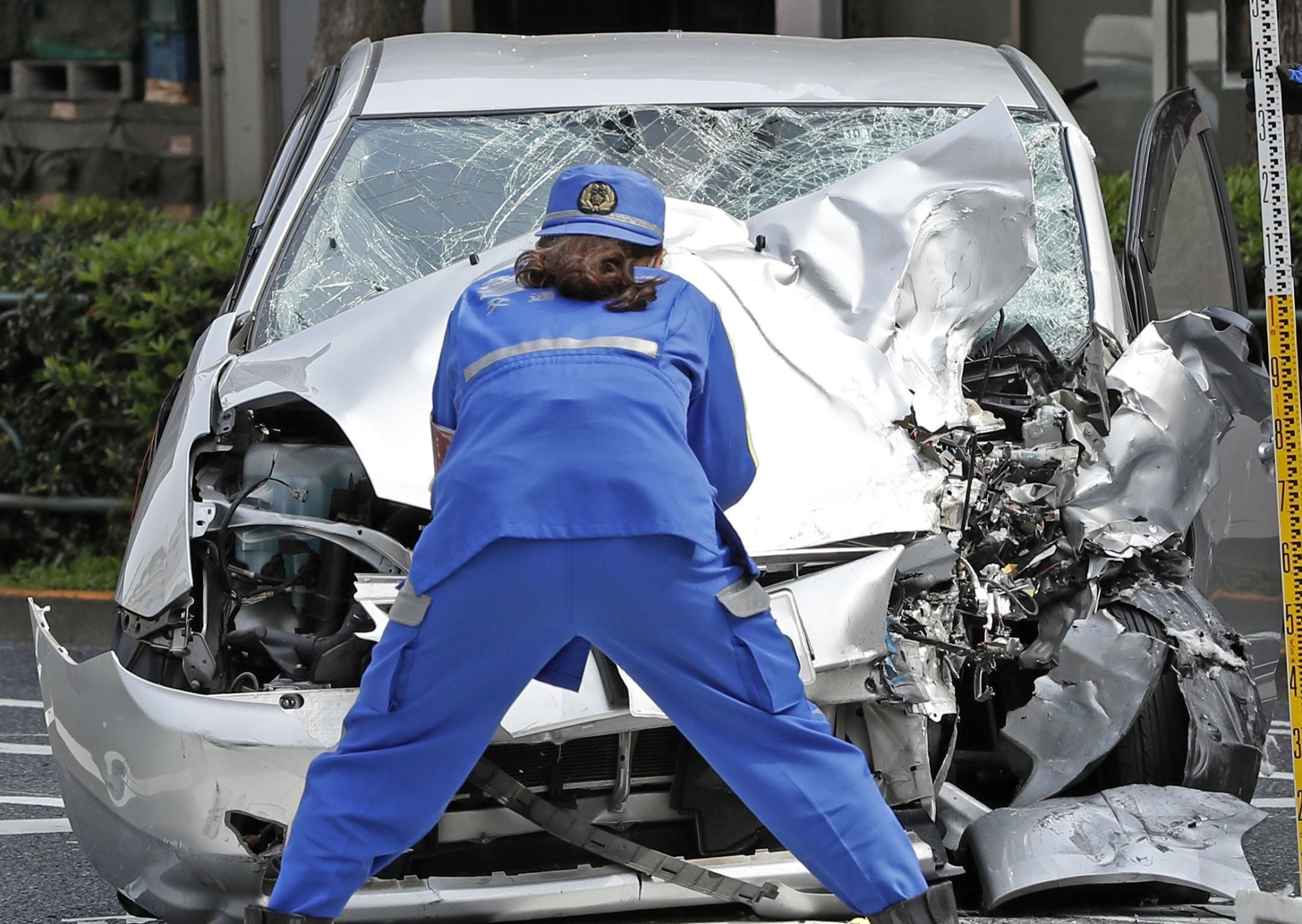 A police officer examines the wreckage of a car that crashed into pedestrians in Tokyo's Ikebukuro district on Friday. | KYODO