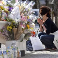 A woman prays at the site of a fatal car crash in Tokyo's Ikebukuro district on Saturday. A woman and her daughter were killed and eight others were injured the previous day after a car driven by an 87-year-old man rammed them. | KYODO