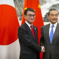 Foreign Minister Taro Kono shakes hands with Chinese counterpart Wang Yi after arriving for a meeting at the Diaoyutai State Guesthouse in Beijing on Monday. | AP