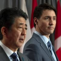 Canadian Prime Minister Justin Trudeau looks on as Prime Minister Shinzo Abe responds to a question during a visit to Parliament Hill in Ottawa on Sunday. | AP