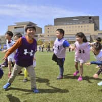 Children exercise at the J-Village national soccer training center in the town of Naraha, Fukushima Prefecture, on Saturday after it resumed full operations. | KYODO