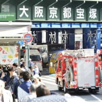Emergency vehicles are seen at the scene of Sunday's fatal bus accident near JR Sannomiya Station in Kobe. | KYODO