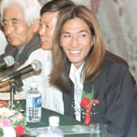 Musician and producer Tetsuya Komuro announces his foray into China's music market at a news conference on Aug. 29, 1997, at the Diaoyutai State Guesthouse in Beijing. | KYODO