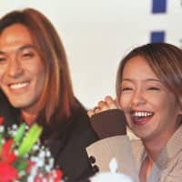 Tetsuya Komuro (left) and pop star Namie Amuro hold a news conference in Beijing in November 1997 before a concert in the city. | ASSOCIATED PRESS