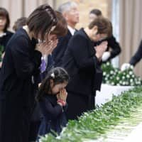 People offer flowers and prayers Sunday at the Kumamoto Prefectural Government office in the city of Kumamoto, where a ceremony was held to commemorate the victims of a series of powerful earthquakes that shook the area three years ago. | KYODO