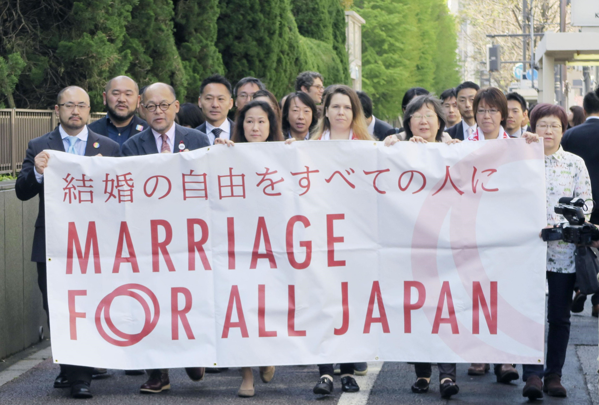Plaintiffs who claim it is unconstitutional not to recognize same-sex marriage hold up a banner before the first oral argument at Tokyo court on Monday. | KYODO