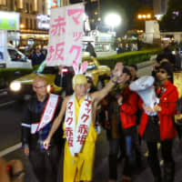 Mac Akasaka (second from left) walks in the Nanba district of Osaka in March 2014 to support Toru Hashimoto, who was running in the Osaka mayoral election. | KYODO