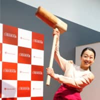 Retired figure skater Mao Asada poses for photos as she prepares to pound steamed rice to make rice cake during an event in Kyoto on Jan. 4, 2018 | KYODO