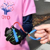 Blind marathon athletes and their guides have to hold a rope throughout the course of the race.   YOSHIAKI MIURA
