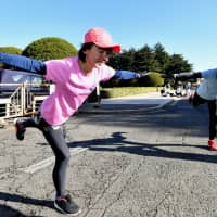 Yoko Aoki works on conditioning her torso during a practice session in Tokyo in December. Aoki runs near her house every day and comes to Jingu Gaien on weekends with her supporters, Team OYO.   YOSHIAKI MIURA