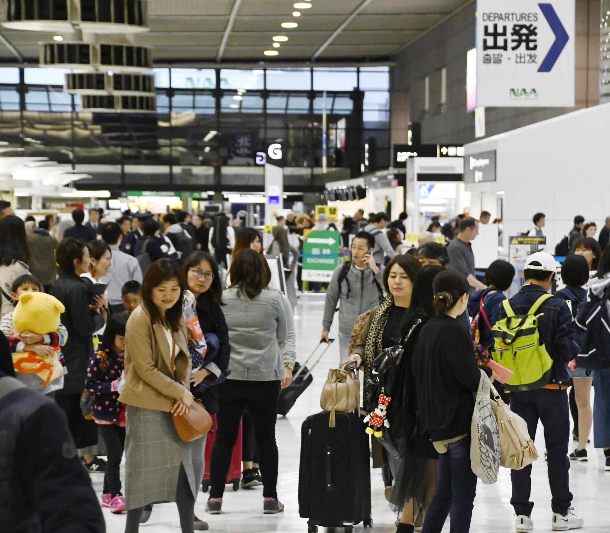 Narita airport's departure lobby in Chiba Prefecture is packed with travelers Friday, a day before a 10-day holiday kicked off. | KYODO