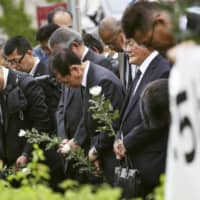 Employees of West Japan Railway Co. and others pray for the victims of a 2005 train derailment that killed 107 people, on the 14th anniversary of the crash in Amagasaki, Hyogo Prefecture, on Thursday. | KYODO